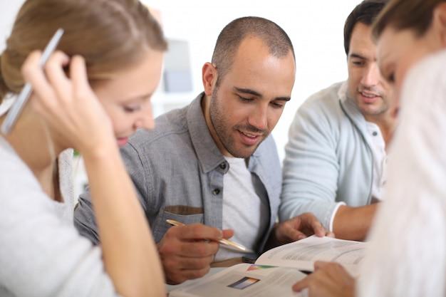 Giovani in college studiando insieme in biblioteca