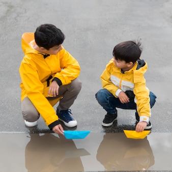 Giovani in impermeabili che giocano con la vista frontale delle barche di plastica