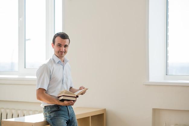 Giovani libri di lettura dello studente maschio a classe o al salone