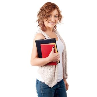 Giovani libri felici della tenuta della ragazza dello studente, studio, istruzione, conoscenza, concetto di scopo