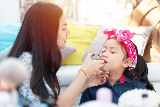 Giovani madre e figlia asiatiche che giocano divertendosi insieme al cosmetico di trucco.