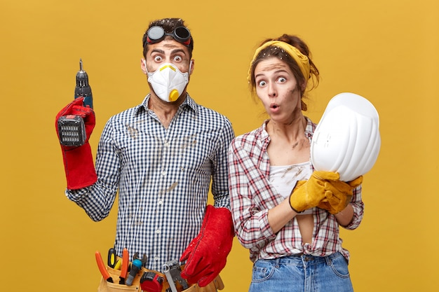 Giovani maestri edili di talento maschi e femmine con sguardi stupiti. uomo di ingegnere civile in maschera protettiva tenendo trapano, cintura di strumenti e sua moglie con il casco