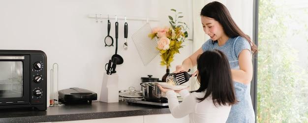 Giovani mamma e figlia giapponesi asiatiche che cucinano a casa. pasta e spaghetti di fabbricazione felici delle donne di stile di vita insieme per il pasto della prima colazione in cucina moderna a casa di mattina.