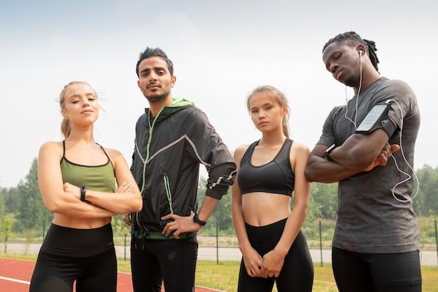 Giovani multiculturali contemporanei in abiti sportivi che ti guardano stando in piedi sullo stadio all'aperto