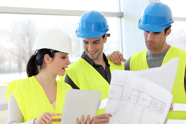 Giovani muratori dei colleghi che esaminano piano della costruzione