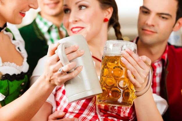 Giovani nel tradizionale bavarese tracht in ristorante o pub