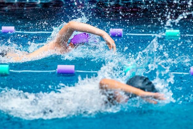 Giovani nuotatori del ragazzo che corrono nello stile libero