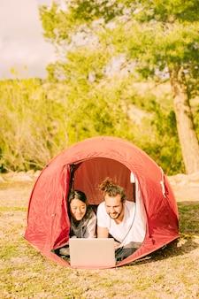 Giovani pantaloni a vita bassa che si rilassano in tenda con il computer portatile