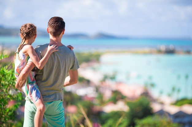 Giovani papà e bambino con la vista della spiaggia bianca tropicale in isola esotica nel mar dei caraibi