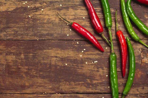 Giovani peperoni rossi e verdi disposti su una vecchia plancia rossa