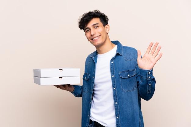Giovani pizze argentine della tenuta dell'uomo sopra la parete isolata che salutano con la mano con l'espressione felice