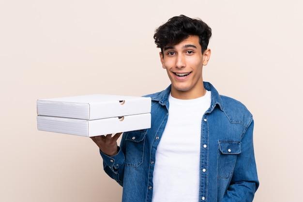 Giovani pizze argentine della tenuta dell'uomo sopra la parete isolata con espressione facciale sorpresa e colpita