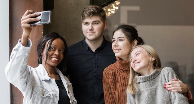 Giovani positivi che prendono insieme un selfie