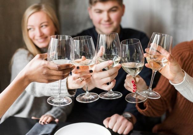 Giovani positivi che tostano i bicchieri di vino