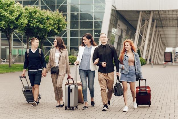 Giovani positivi felici con bagagli all'aperto vicino all'aeroporto.