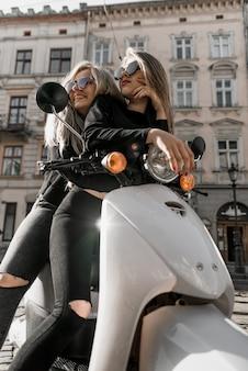 Giovani ragazze allegre con scooter