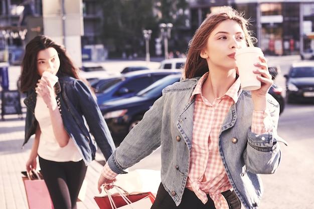 Giovani ragazze attraenti con borse della spesa e caffè in città.