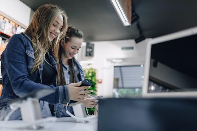 Giovani ragazze attraenti nei telefoni di prova del negozio di elettronica su una finestra del negozio. concetto di acquisto di gadget.