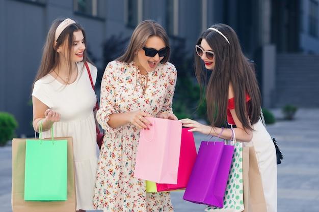 Giovani ragazze con le borse della spesa in città. ragazze che camminano per la città dopo lo shopping. le donne sorridenti tengono in mano i sacchetti colorati. consumismo, acquisti, vendite.
