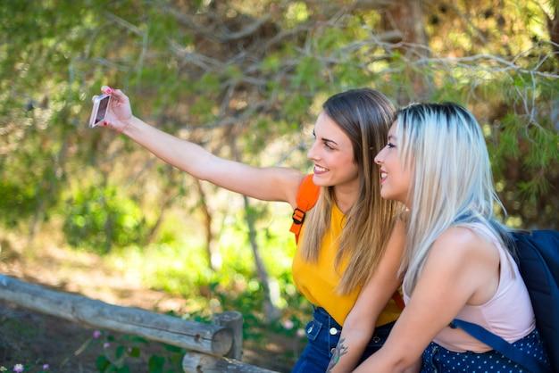 Giovani ragazze dello studente con lo zaino in un parco che fa un selfie