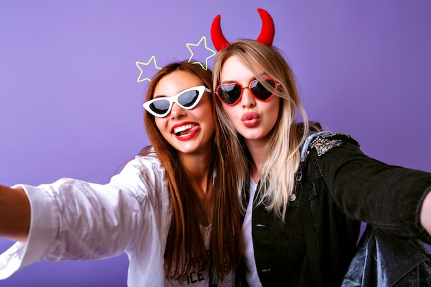 Giovani ragazze divertenti che fanno selfie, occhiali vintage, fasce per capelli da festa con diavolo e stelle, vestiti casual per giovani, umore positivo.