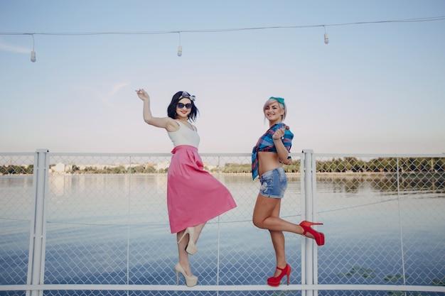 Giovani ragazze in posa con una gamba alzata su una rete fissa bianca