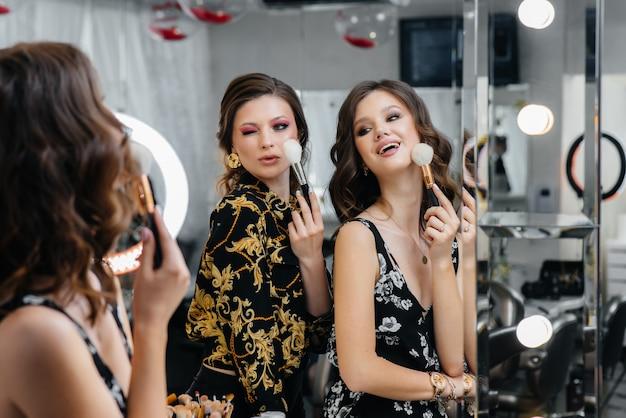 Giovani ragazze sexy si divertono e si truccano per una festa davanti allo specchio. moda e bellezza.