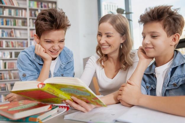 Giovani ragazzi gemelli felici divertendosi con la loro mamma mentre studiando