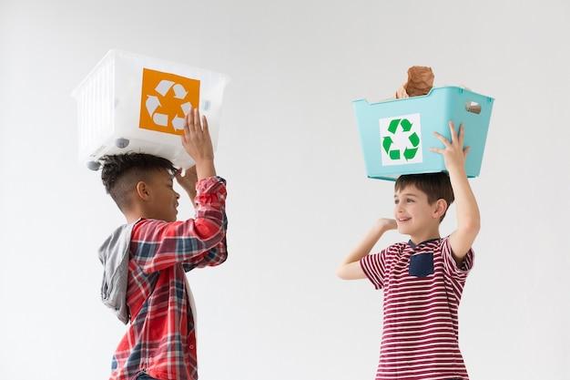 Giovani ragazzi svegli che tengono le scatole di riciclaggio