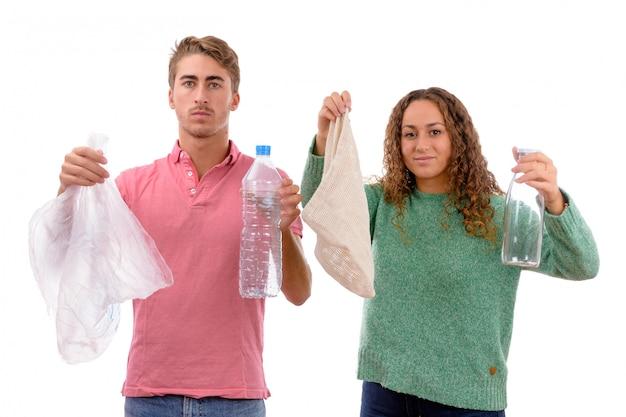 Giovani ragazzo e ragazza caucasici con una borsa del panno e una bottiglia di vetro da riutilizzare e sacchetto di plastica e bottiglia al riciclaggio isolati