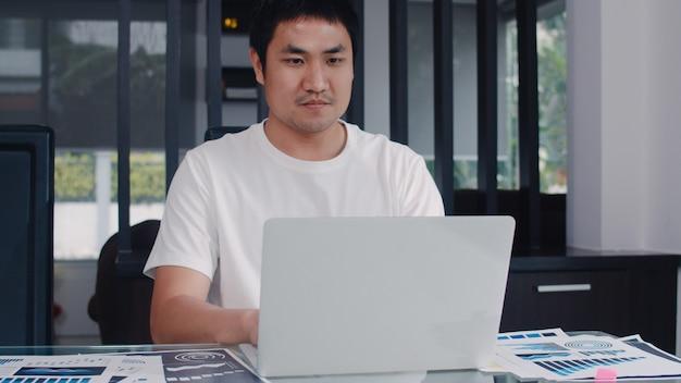 Giovani record asiatici dell'uomo di affari di entrate e spese a casa. maschio preoccupato, serio, stress durante l'utilizzo del budget record portatile, fiscale, documento finanziario che lavora nel salotto di casa.