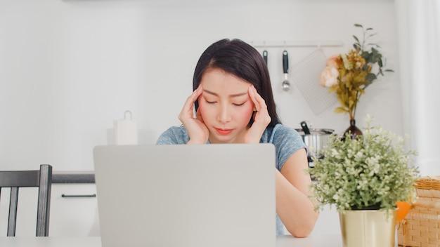 Giovani record asiatici della donna di affari di entrate e spese a casa. signora preoccupata, seria, stress durante l'utilizzo del budget record del laptop, fiscale, documento finanziario che lavora nella cucina moderna a casa.