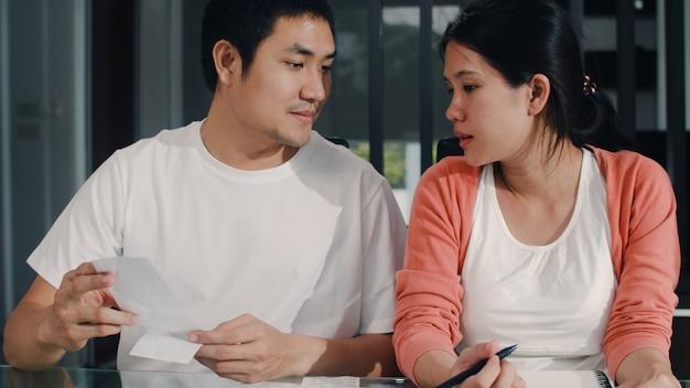 Giovani record incinti asiatici delle coppie delle entrate e delle spese a casa. mamma e papà felici utilizzando il budget record del computer portatile, tasse, documento finanziario, commercio elettronico che lavora nel salotto di casa.