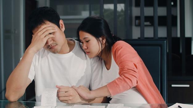 Giovani record incinti asiatici delle coppie delle entrate e delle spese a casa. papà preoccupato, serio, stress mentre record di bilancio, tasse, documenti finanziari che lavorano nel salotto di casa.