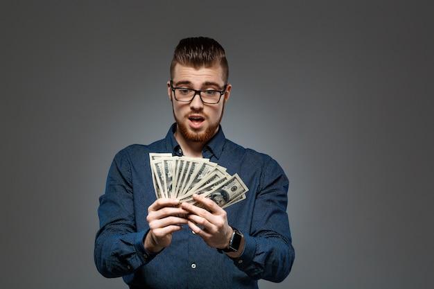 Giovani riusciti soldi della tenuta dell'uomo d'affari sopra la parete scura.