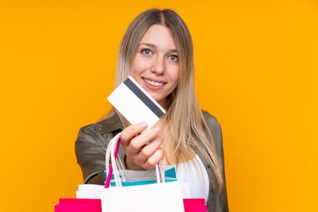 Giovani sacchetti della spesa biondi della tenuta della donna e una carta di credito