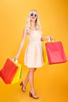 Giovani sacchetti della spesa biondi sorridenti della tenuta della donna.