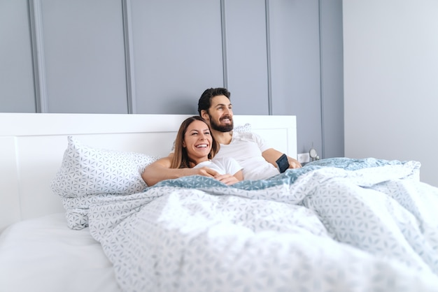 Giovani sorridenti coppie caucasiche attraenti felici sdraiato a letto e guardare la televisione al mattino. interno camera da letto.