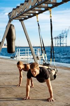 Giovani sportivi che si allenano con trx vicino al mare al mattino.