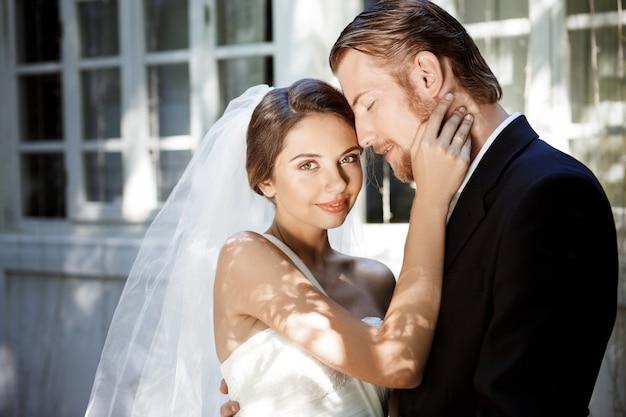 Giovani sposi belli sorridenti, godendo, abbracciando.