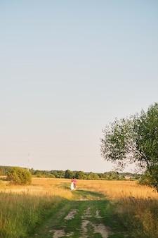 Giovani sposi camminando sul campo. giorno nuvoloso di stile retrò abito soffice