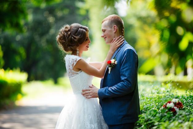 Giovani sposi favolosi che posano nel parco il giorno soleggiato.