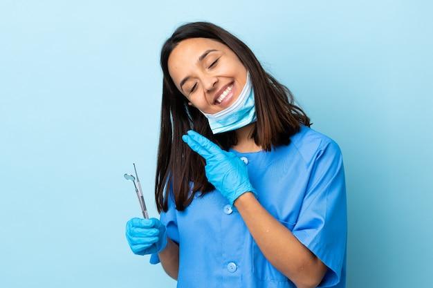 Giovani strumenti di tenuta castana della donna del dentista della corsa mista sopra sorridere isolato e mostrare il segno di vittoria