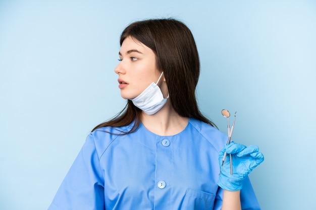 Giovani strumenti di tenuta della donna del dentista sopra la parete blu che sembra laterale