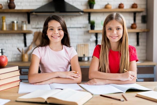Giovani studentesse sorridenti che si siedono allo scrittorio e che si esercitano a casa