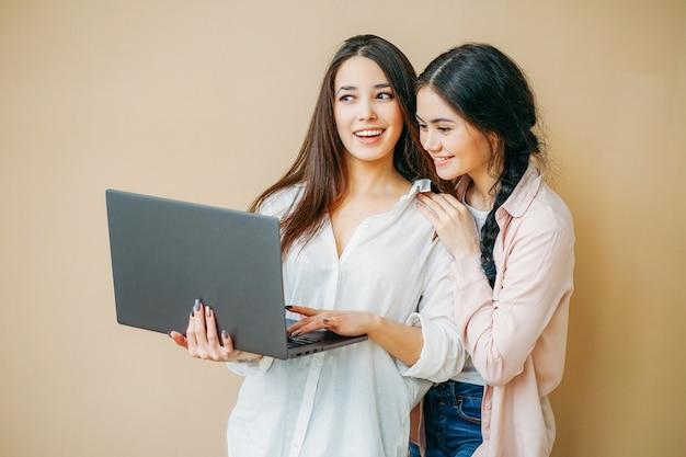Giovani studentesse sorridenti in casuale con il computer portatile in mani isolate su fondo beige