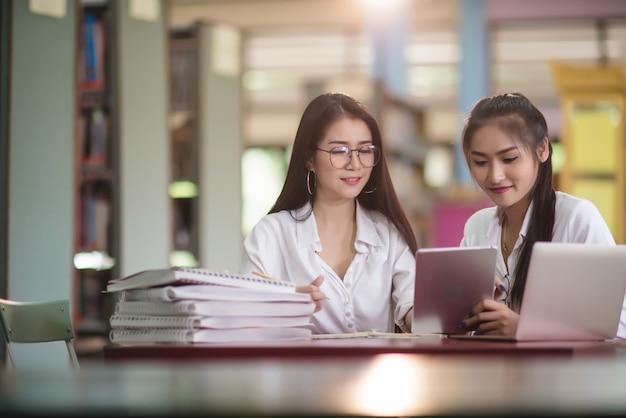 Giovani studenti che imparano, scaffali di biblioteca