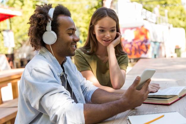 Giovani studenti multietnici felici degli amici che parlano a vicenda
