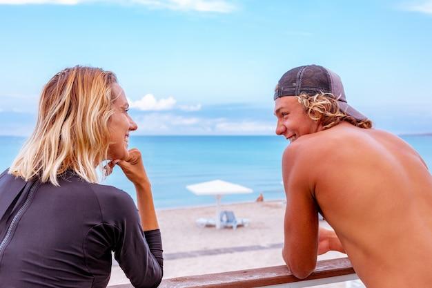 Giovani surfisti attivi sorridenti delle coppie che si rilassano sulla spiaggia dopo lo sport