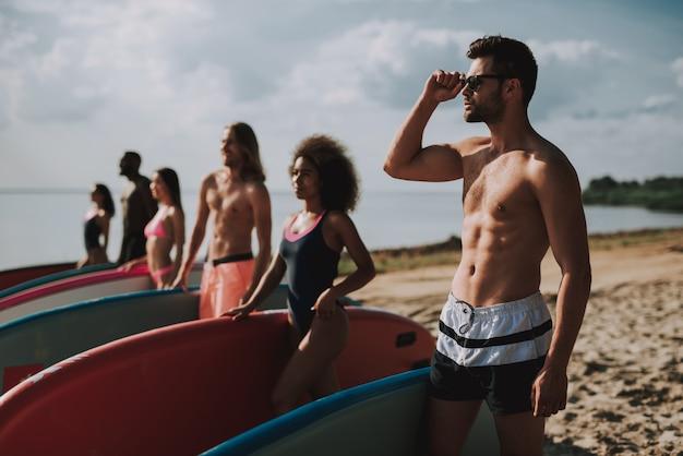 Giovani surfisti in costumi da bagno in piedi in spiaggia.